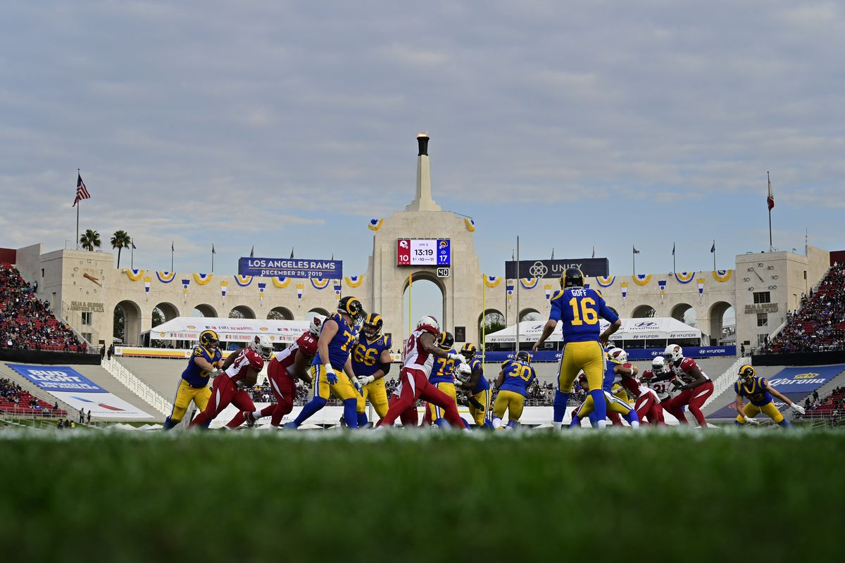 Jared Goff #16 watches as Todd Gurley #30 of the Los Angeles Rams runs the ball against the Arizona Cardinals at Los Angeles Memorial Coliseum on December 29, 2019 in Los Angeles, California.