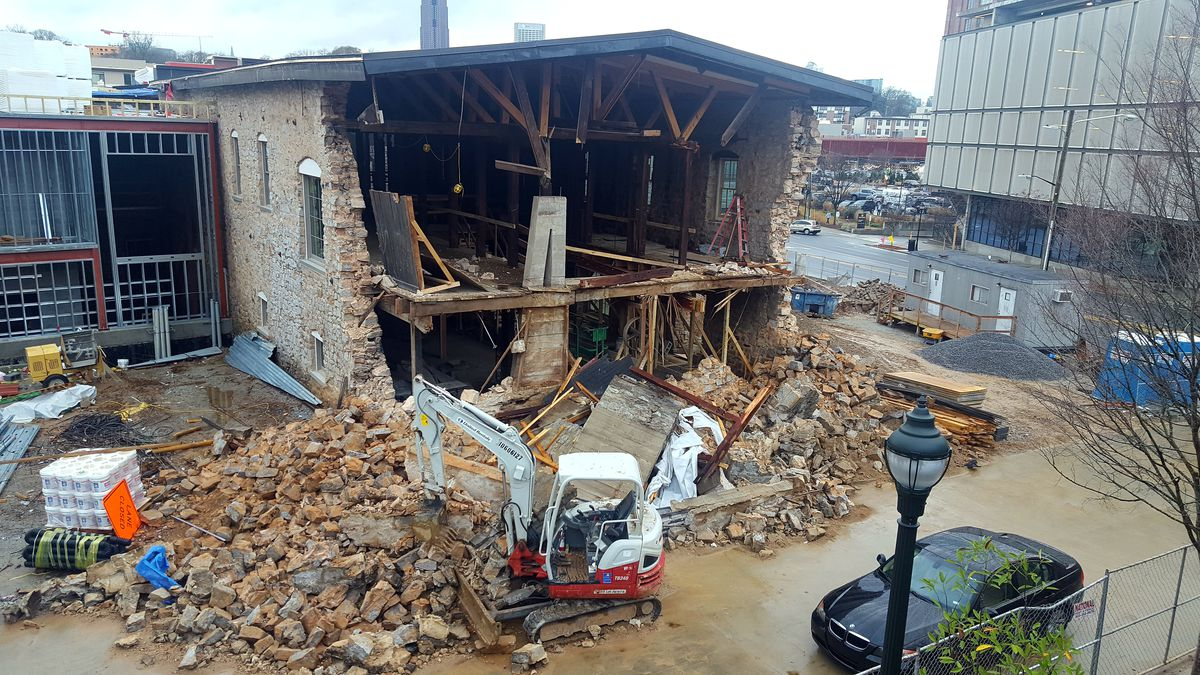 Rubble sits at the foot of the old building, in front of a backhoe and other construction equipment.