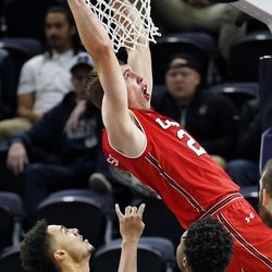Utah Utes forward Tyler Rawson is fouled while attempting to dunk against the Utah State Aggies during NCAA basketball at Vivint Smart Home Arena in Salt Lake City on Saturday, Dec. 9, 2017.