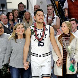 Utah State guard Abel Porter walks out onto the court on Senior Night with his wife, Presley, and parents Abel and Martha Porter on Feb. 25 at the Spectrum in Logan.