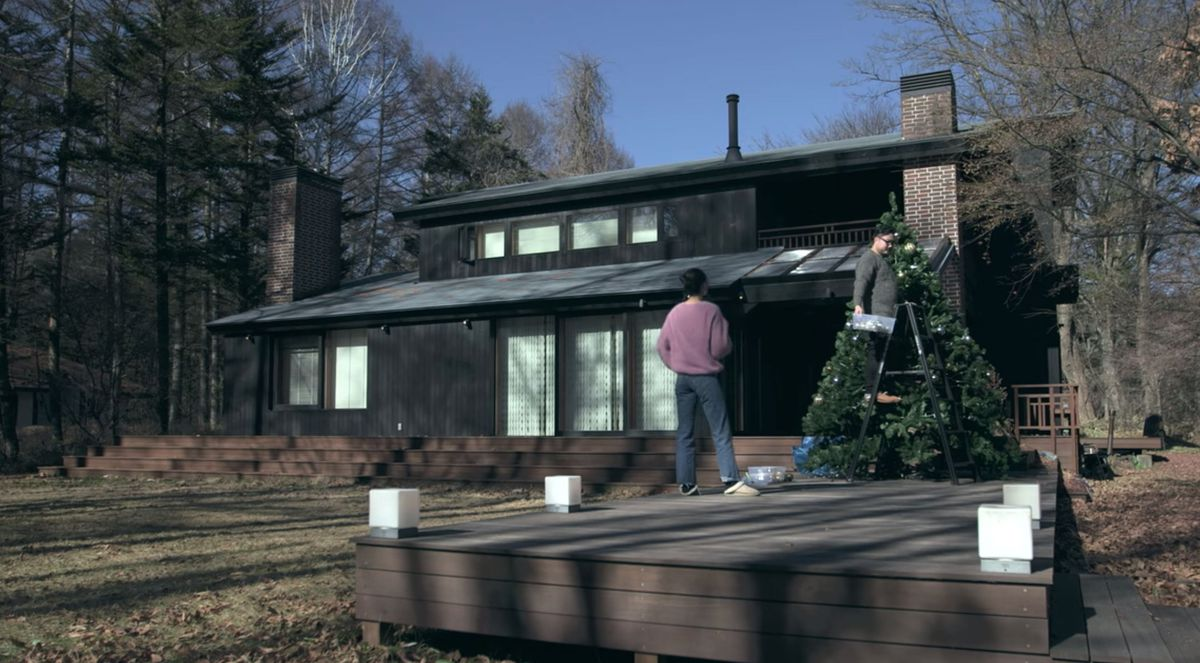 In the foreground, a person is standing on a ladder decorating a Christmas tree. There is a person standing next to the ladder on a wooden deck. In the background is a house with a painted black facade. The house is surrounded by trees.