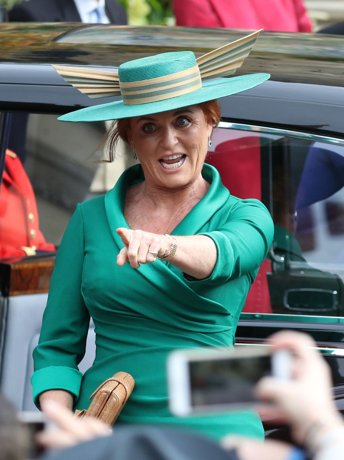 Sarah Ferguson points to someone in a crowd of onlookers.