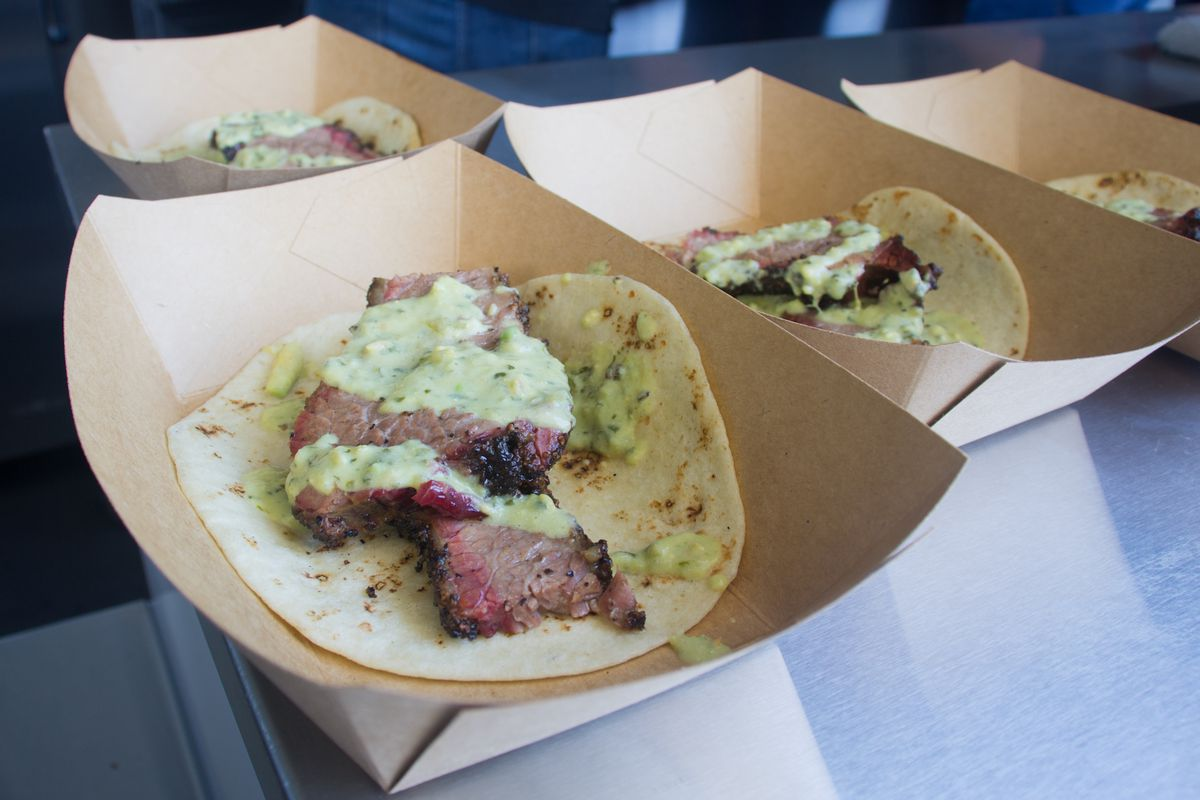 Paper containers with open-face flour tortillas topped with thick slices of brisket and a green creamy sauce