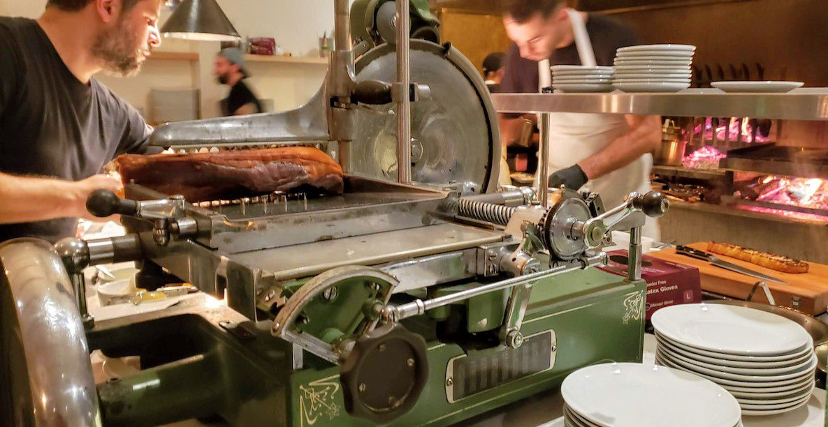 Chad Colby uses a vintage meat slicer to serve antipasti at Antico