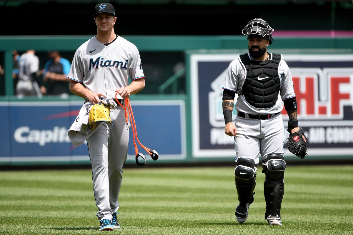 Trevor Rogers #28 and Sandy Leon #7 of the Miami Marlins walk on the field prior to the game against the Washington Nationals at Nationals Park on May 02, 2021 in Washington, DC.