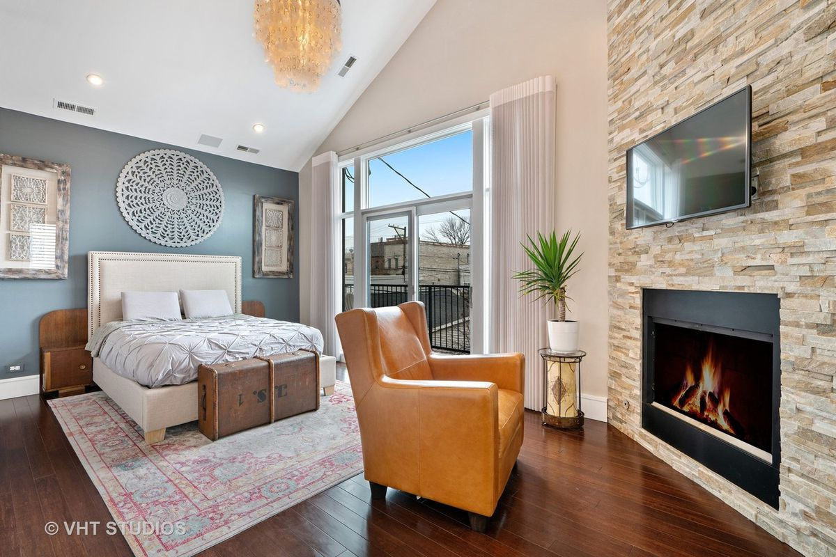 A stone fireplace with a leather chair nearby. Behind that, a king-sized bed against an grey accent wall near a window that lets out onto a balcony.
