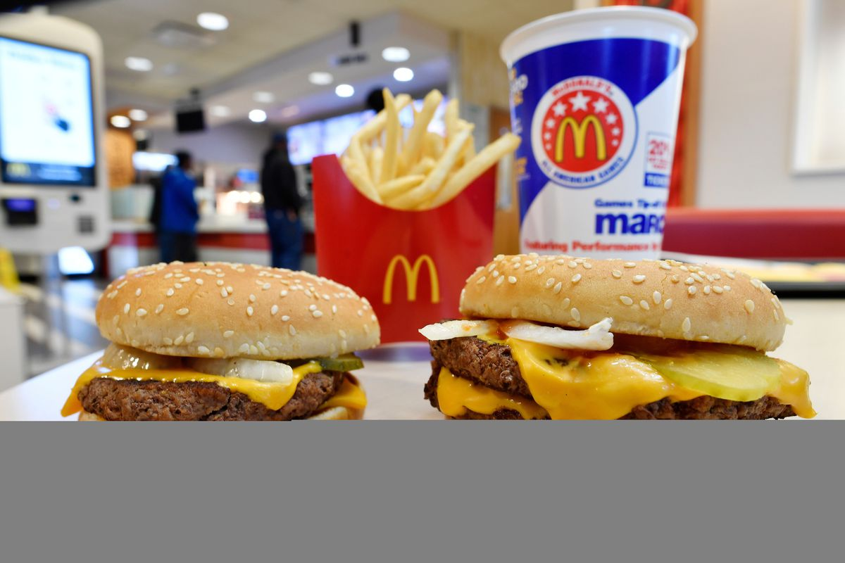In this March 6, 2018, file photo, a McDonald's Quarter Pounder, left, and Double Quarter Pound burger is shown with fresh beef in Atlanta. The fast-food chain is doing a Throwback Thursday promotion, offering some food items for 35 cents or less.