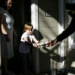 Amelia Young, 4, and her mother, Becky, accept a lunch box from Glendale teacher Lucas Tucker at their residence at Seasons at Pebble Creek in Salt Lake City on Tuesday, Dec. 29, 2020. Publik Kitchen cooked almost 300 meals over three days for Glendale Middle School students and their families through the Nourish to Flourish initiative. The initiative, which started in response to the COVID-19 pandemic, is a partnership between restaurants, service organizations and community funders to provide meals to those in need.