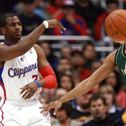 Los Angeles Clippers' guard Chris Paul, left, makes a pass as he is defended by Utah Jazz's guard Devin Harris during the first half of a NBA basketball game in Los Angeles, Saturday, March 31, 2012.  (AP Photo/Ringo H.W. Chiu)