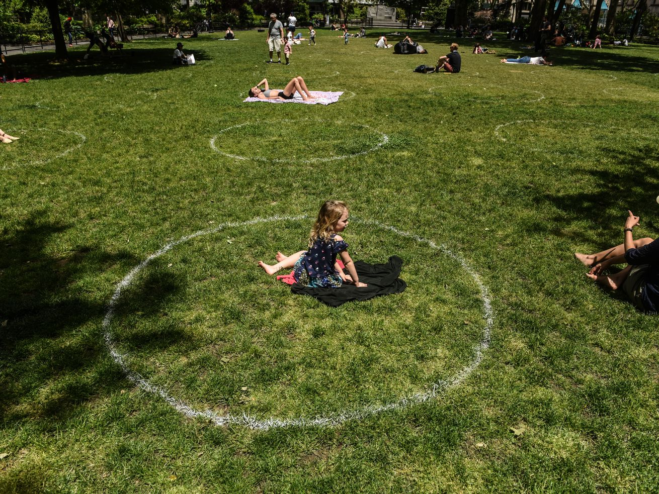 A young girl sits inside a social distancing circle at a New York City park on May 22, 2020, during the Covid-19 pandemic.