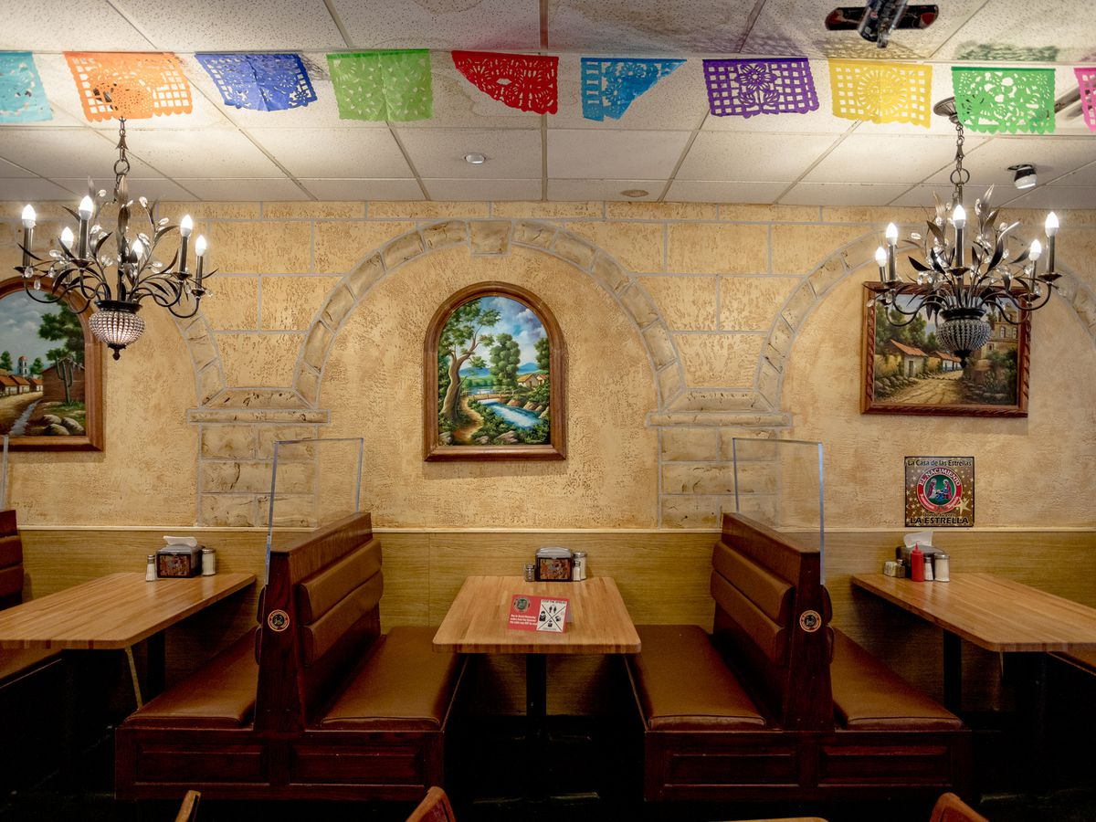 Booth seats surround wooden tables along a wall at Taqueria El Nacimiento. The booths are separated by plexiglass.