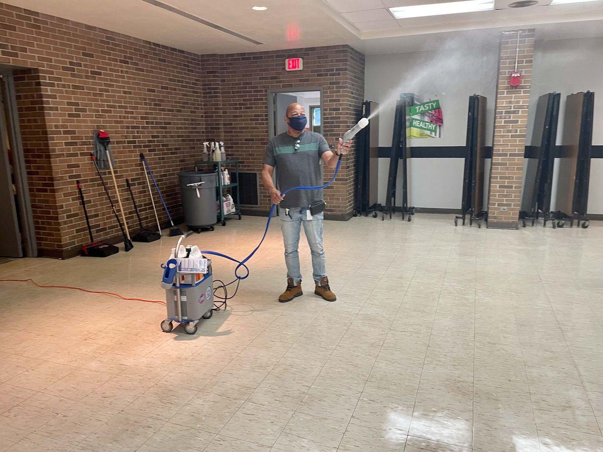 A custodian disinfectants a school cafeteria using a sprayer.