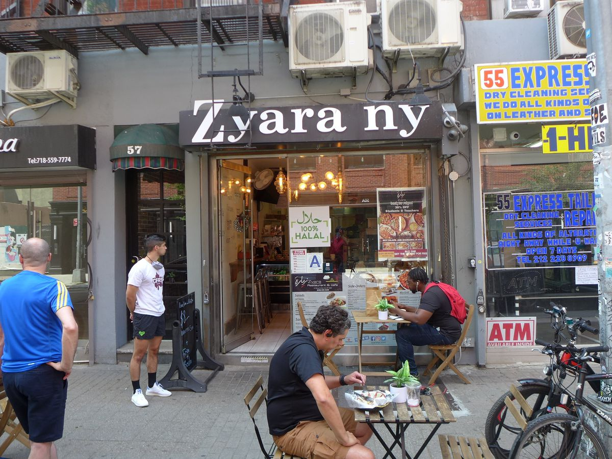 A Middle Eastern restaurant with two tables set out on the sidewalk.