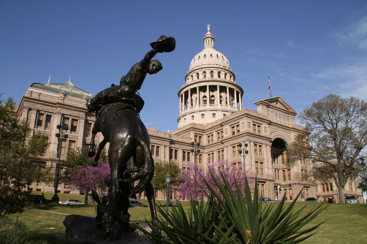 Texas Capitol building with statue of a cowboy and some blooming yucca plants out front