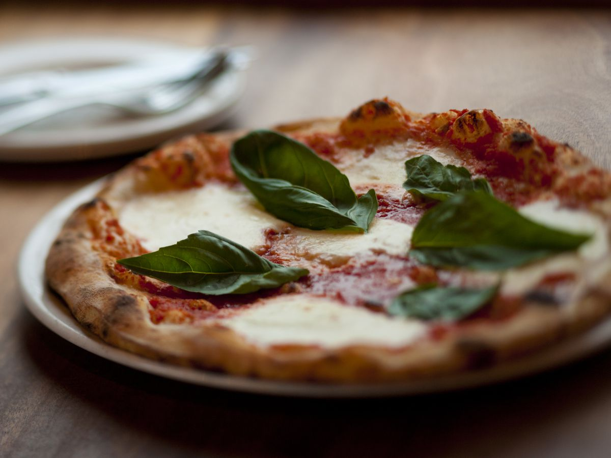 A pizza with mozzarella and basil sits on a wooden table next to silverware at Nostrana.