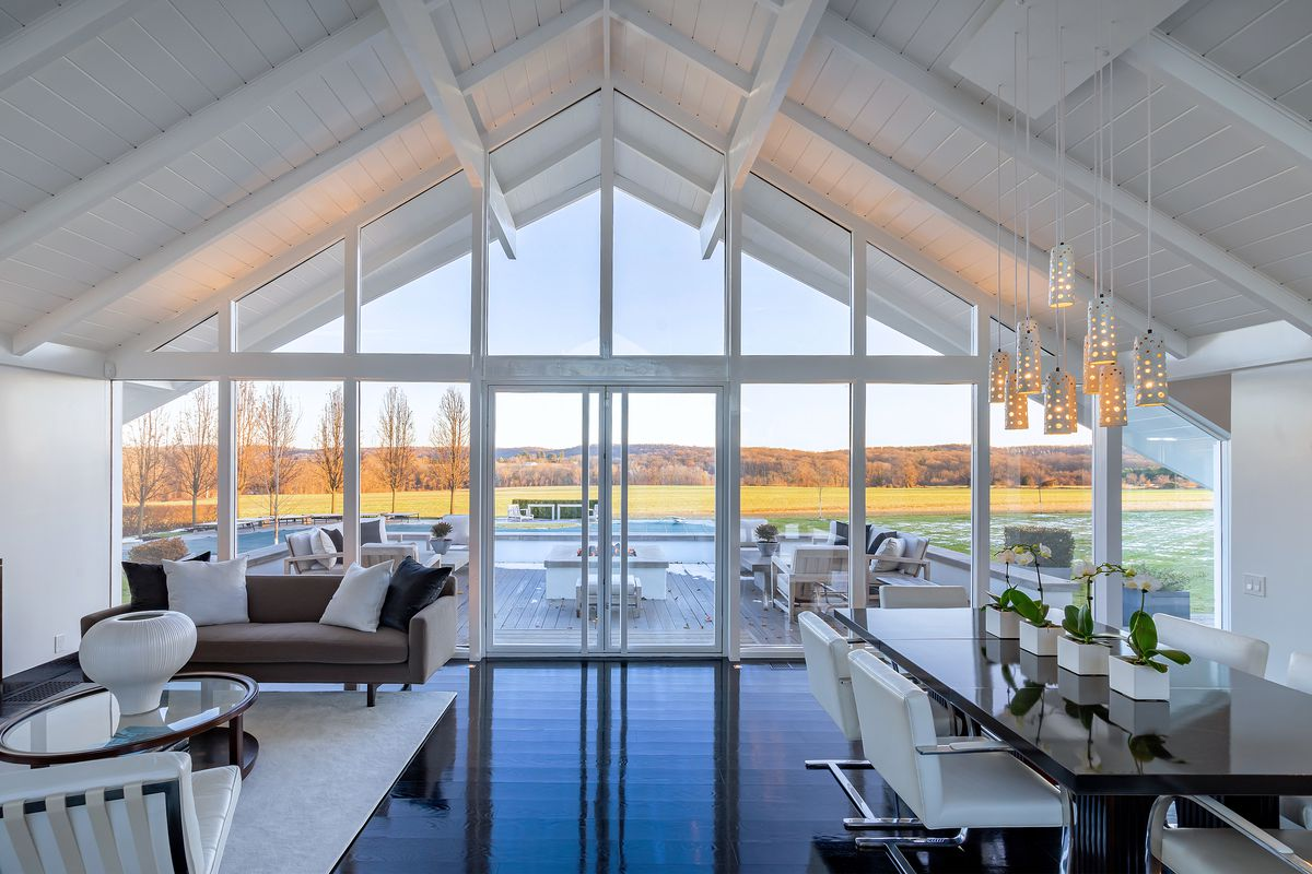 A double-height living room has vaulted ceilings with white beams, large windows, a dining room table, and views to the outdoors.