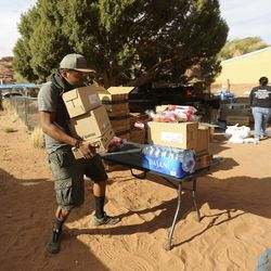 Chad Valentine carries boxes of food while volunteering at a drive-thru food bank, organized by Transitions Pantry, in Oljato-Monument Valley, San Juan County, on Thursday, April 30, 2020. The Navajo Nation has one of the highest per capita COVID-19 infection rates in the country.