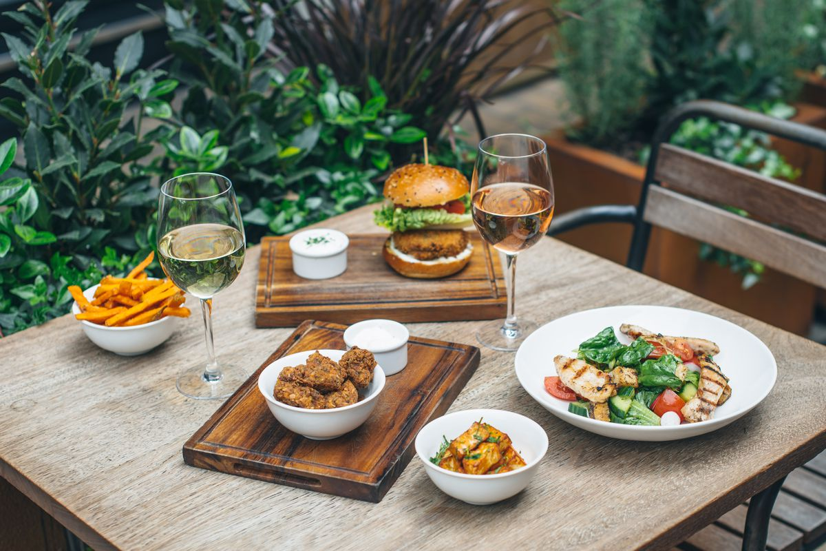 Free-range chicken burgers and salads with wine at Whyte and Brown, the free-range chicken restaurant in Kingly Court, Soho