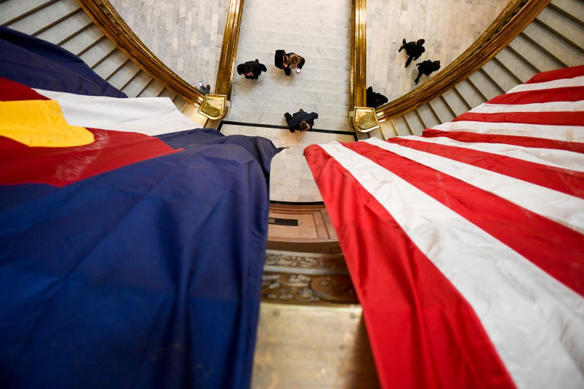 A Colorado state flag hangs next to a United States flag high above an entry way as people walk down a hallway.