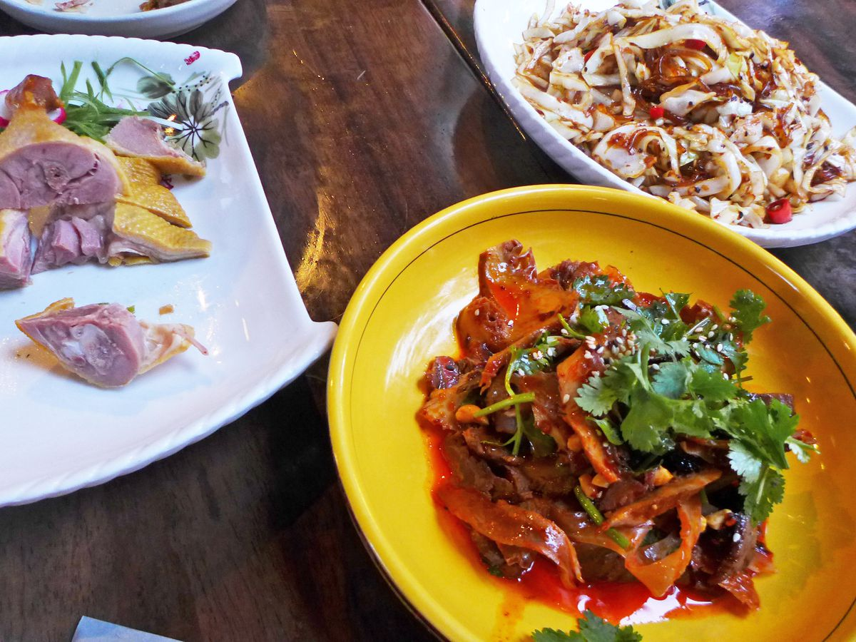 Three Chinese dishes involving duck, noodles, and beef tripe on colorful plates and bowls.
