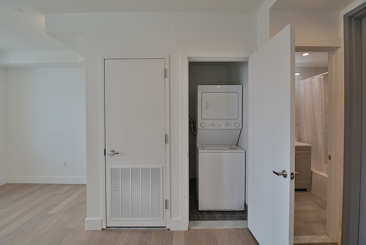 A small closet with a washer/dryer inside.
