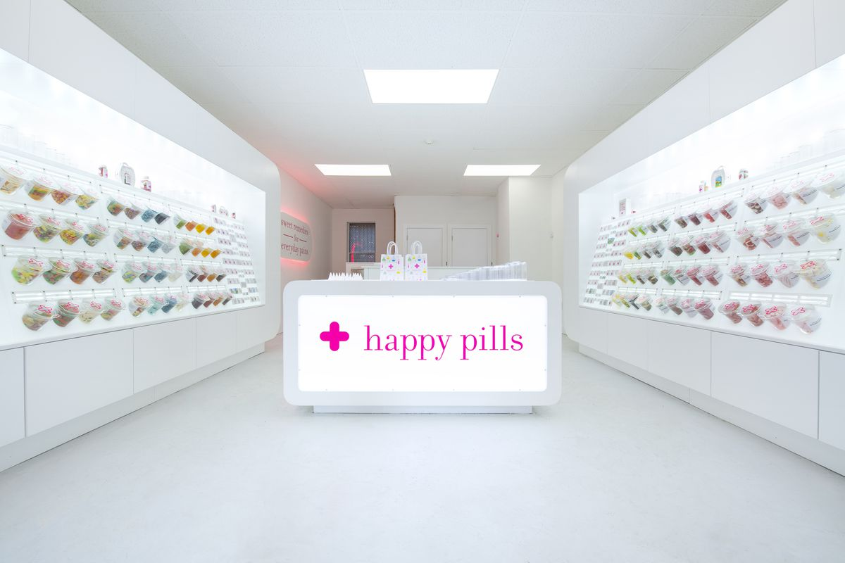 """Interior of a bright white candy store with a pharmacy theme. A counter in the middle has a pink logo that reads """"Happy Pills,"""" and each wall is lined with bulk candy containers."""