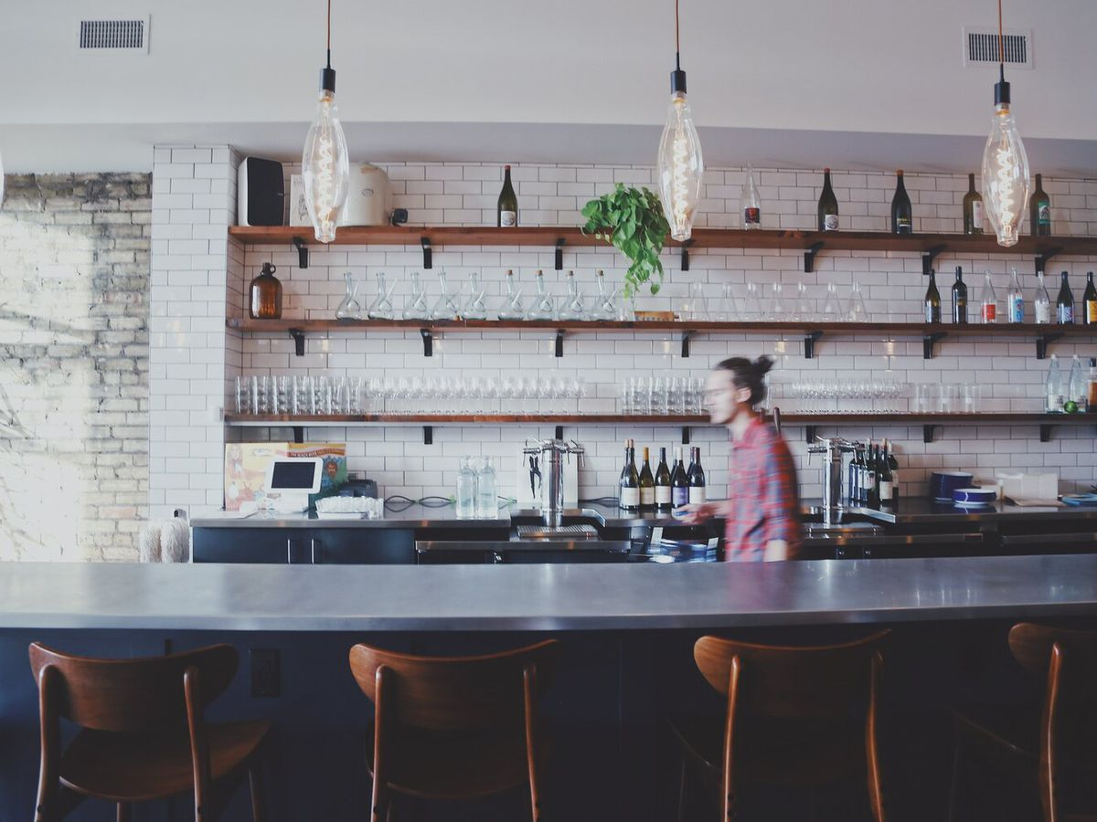 A man walks behind a bar flanked by white subway tile, open shelves hold wine glasses, and a metal-topped bar is lined with bar chairs