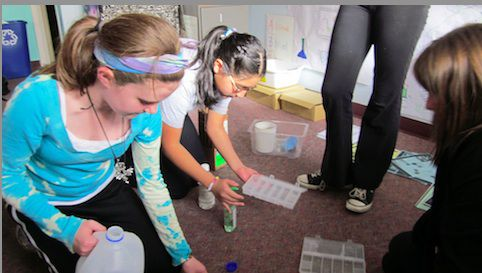 Sixth-graders study pH levels in science class at GALS, an all-girls Denver charter school.