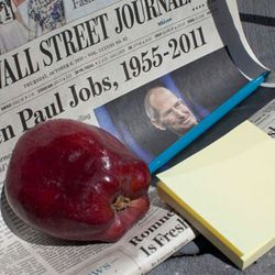 NEW YORK, NY - OCTOBER 06:  A copy of the Wall Street Journal and an apple are left in remembrance to Steve Jobs, founder and former CEO of Apple Inc., outside the Apple Store on West 14th Street on October 6, 2011 in New York City. Jobs, who died October