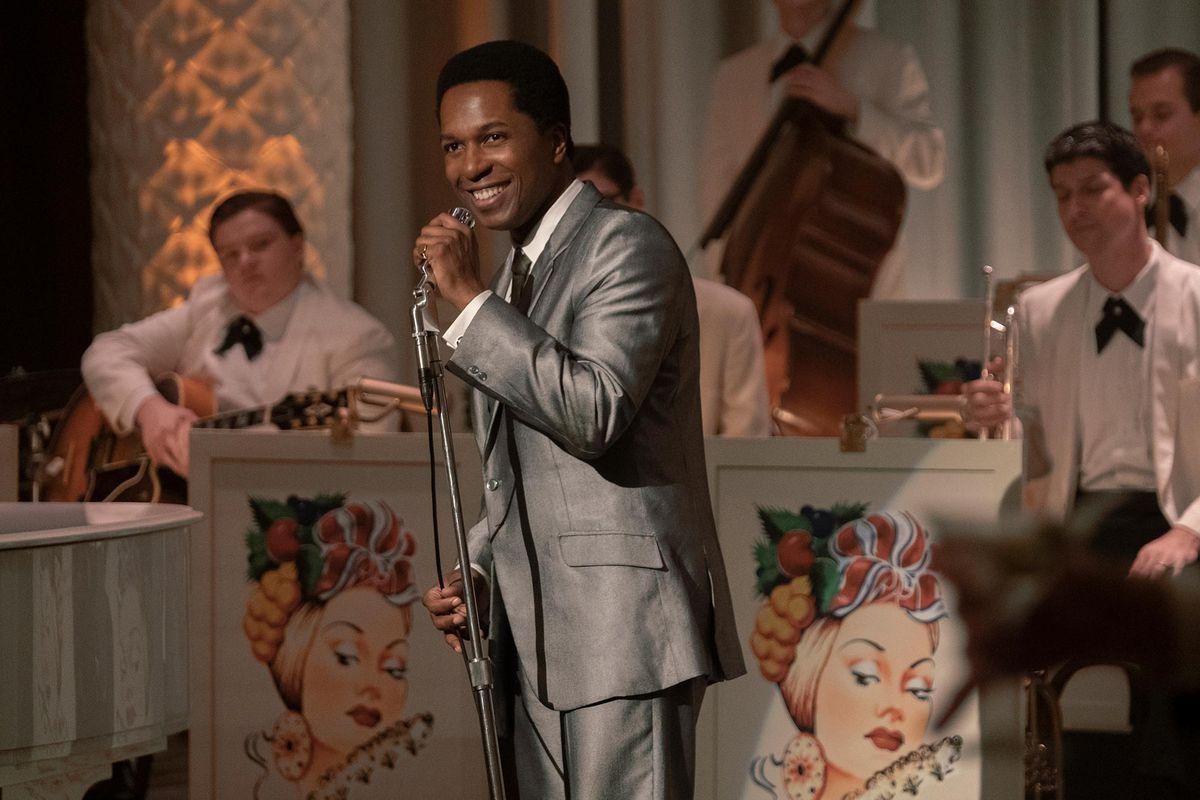 leslie odom jr. sings into a mic
