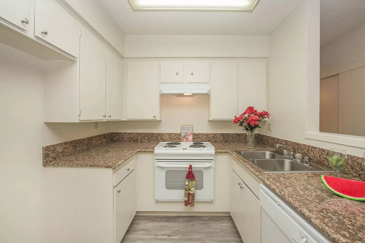 A kitchen with granite countertops and a white stove