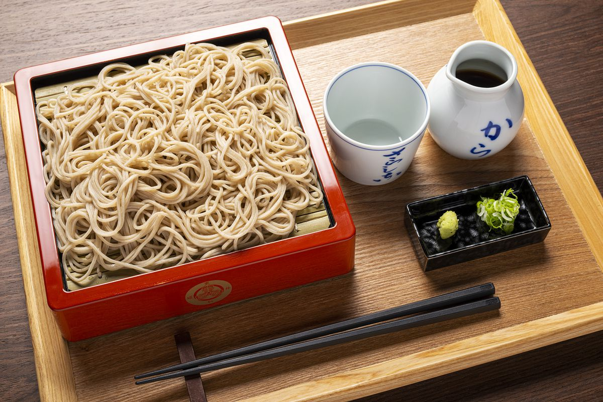 A plate of light-brown noodles appear in a meal set alongside a pair of chopsticks, a side of wasabi and ginger, and a white cup