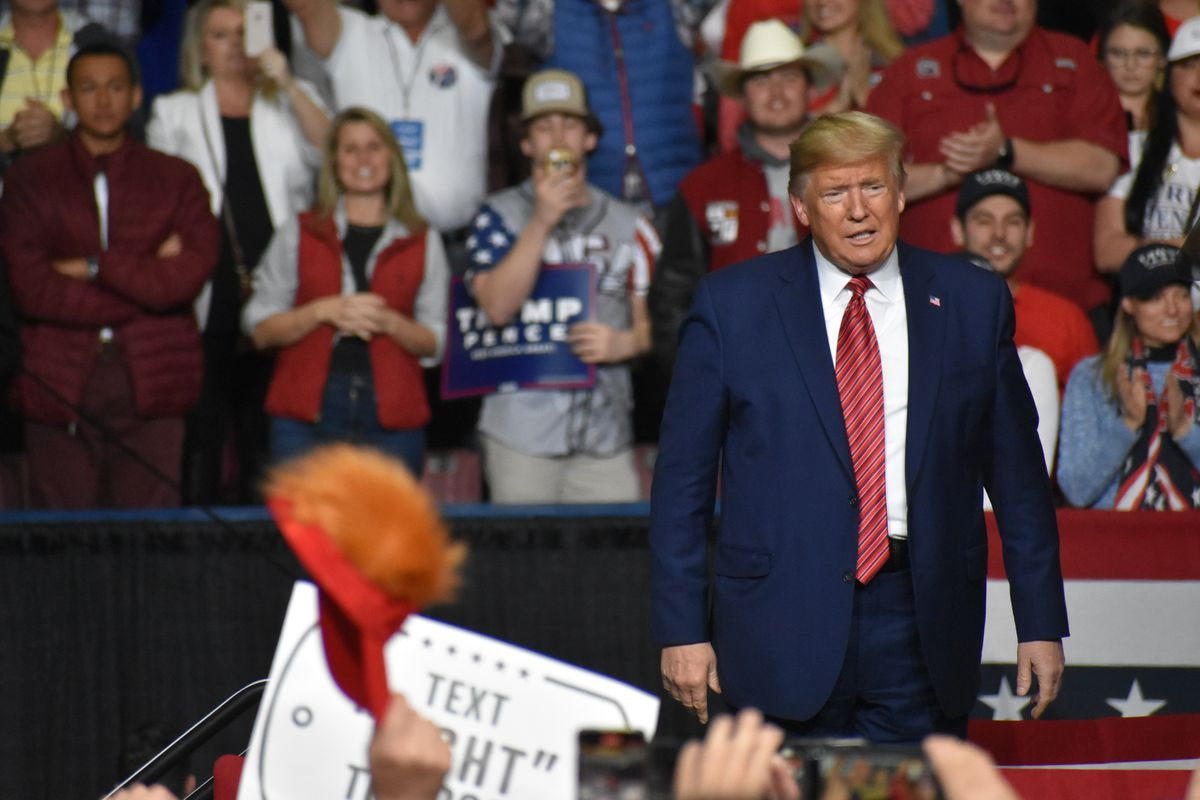 Trump looks at a crowd of supporter holding Trump-Pence signs, and waving red hats.