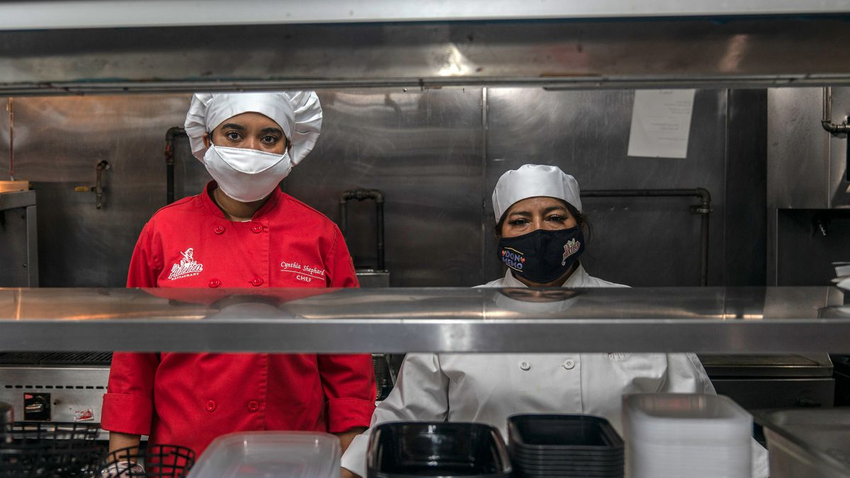 Cynthia Shephard (left) and Maria Iglesias prepare for the day in the kitchen of their restaurant, El Corazon de Mexico, in Long Island City, July 17, 2020.