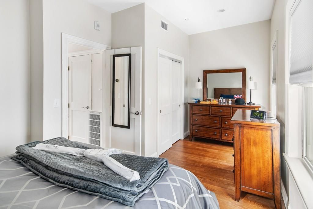 A bedroom with furniture, a door open to the bathroom, and a closed closet door.