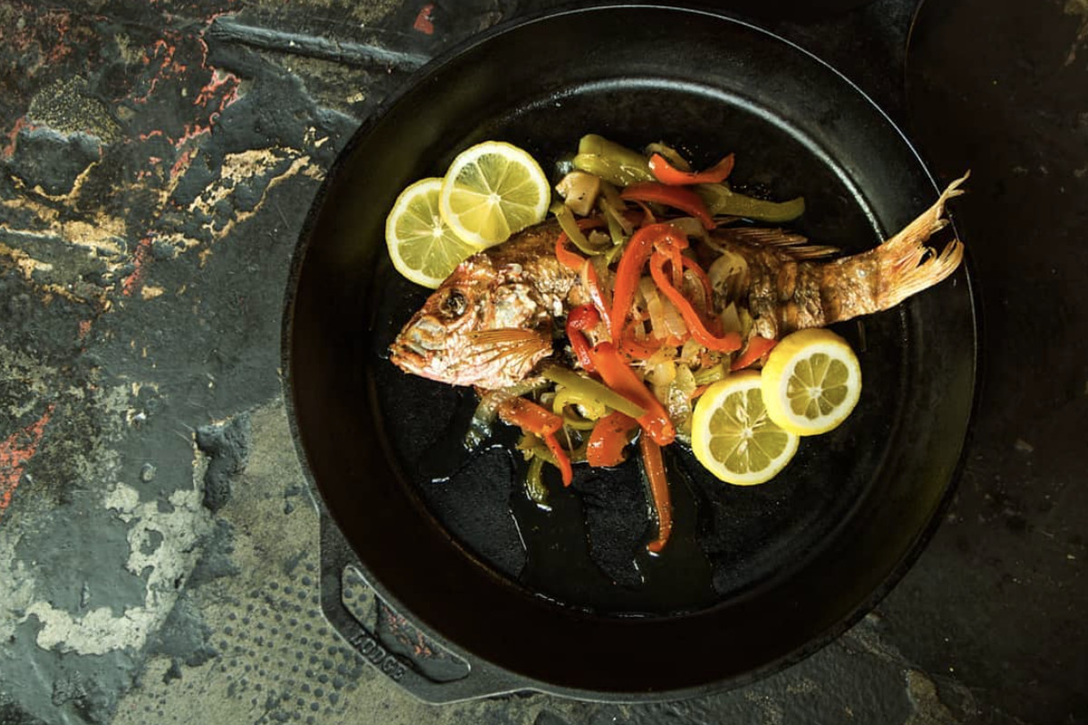 A top-down view of Escovitch snapper topped with peppers and slices of lemon