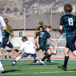 Farmington's Trey Hammond (22) steals the ball from Olympus during a high school boys soccer game at Farmington High School on Thursday, March 18, 2021.