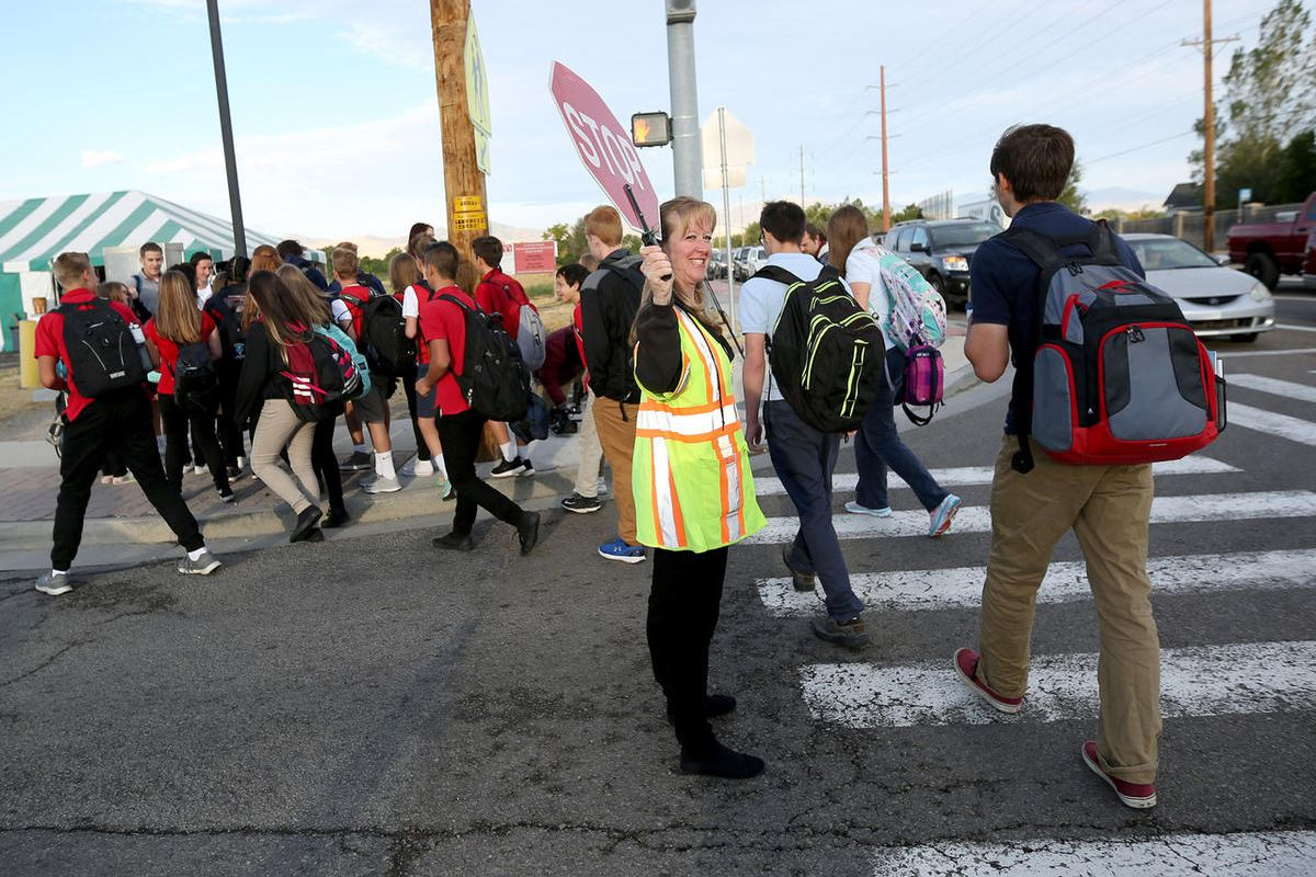 Crossing guard Heather Childs helps students cross the street near Hawthorn Academy and Westvale Elementary School in West Jordan on Wednesday, Sept. 14, 2016.