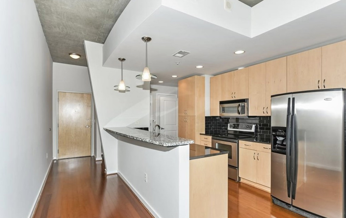 Kitchen with light wood cabinets, stainless appliances, and hardwood floors.