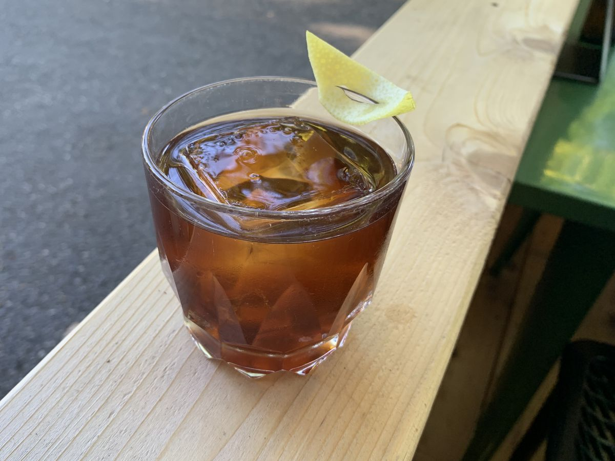 A chunky rocks glass sits on a wooden fence. The drink within is a dark brown over a clear ice cube.