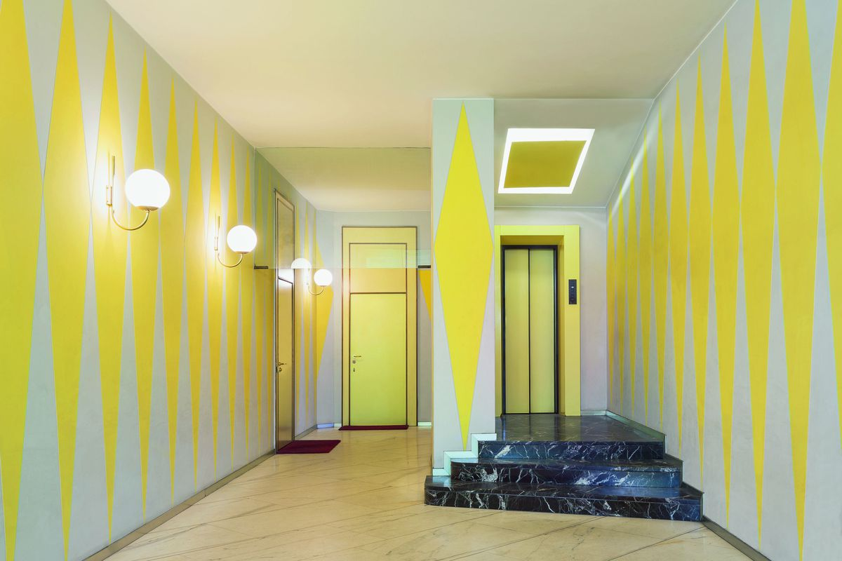 An entryway with light walls and yellow geometric diamond shapes contrast against light marble floor and dark marble steps.