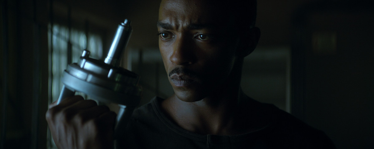 Anthony Mackie as an android in Outside the Wire examines a silver tool