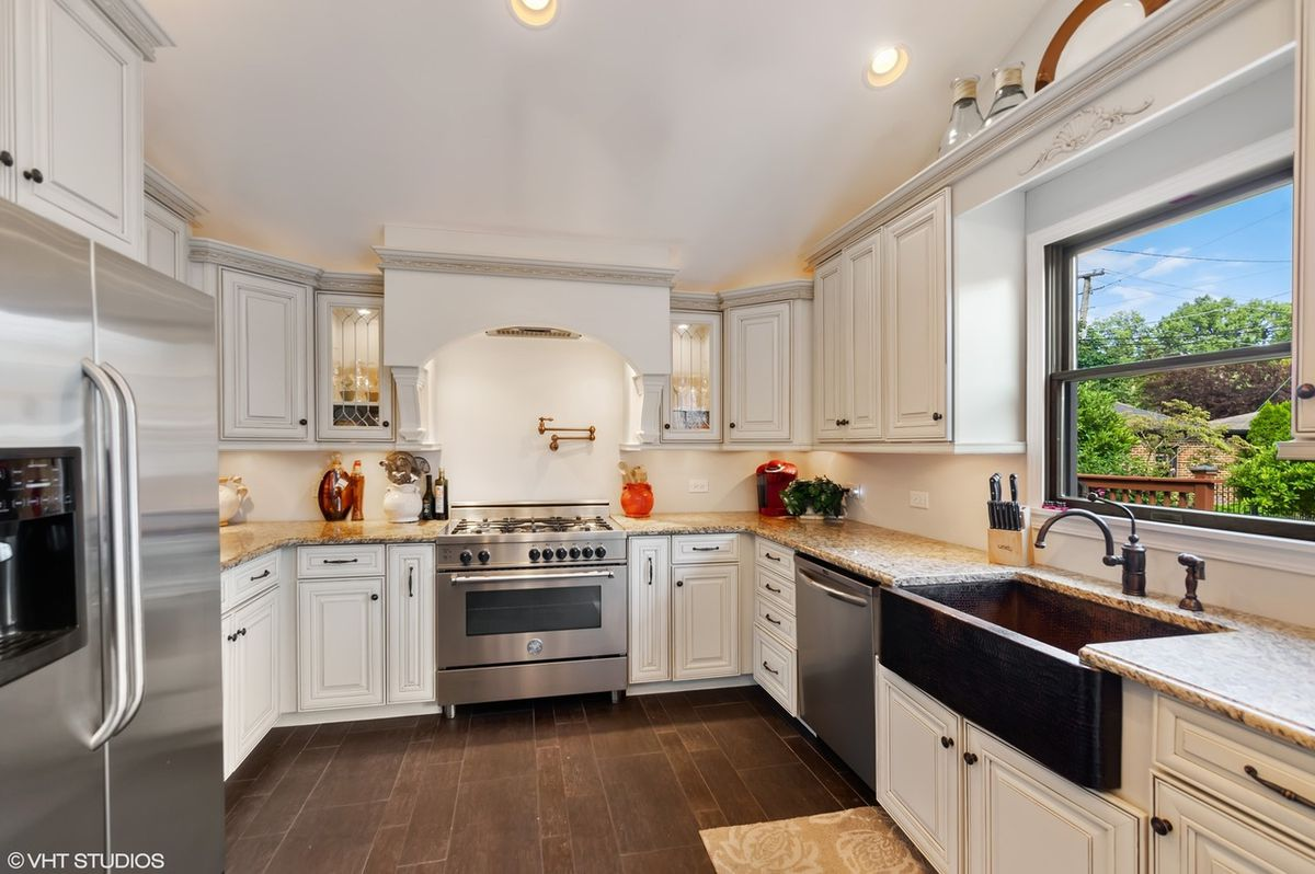 A provencal style kitchen with traditional cream cabinets and steel appliances.