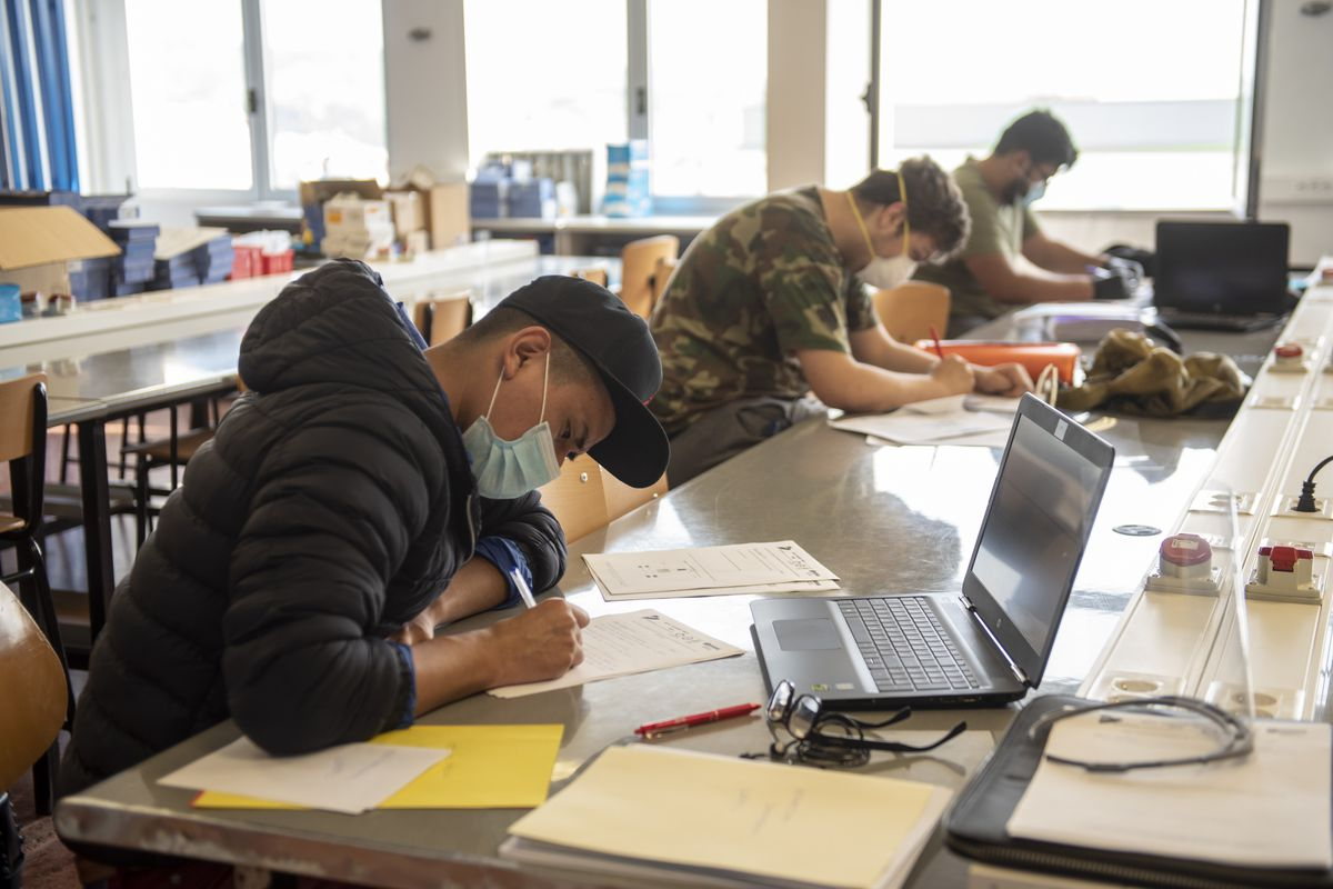 Three male students wearing masks sitting spaced out at a long table working on papers