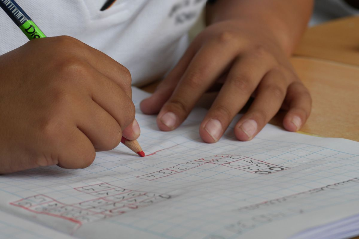 Close up of a student writing in a graphing notebook.