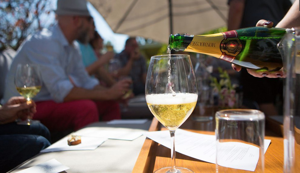 A glass of champagne being poured at a bright summer table.