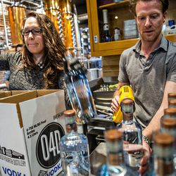 Jeff Moore uses a heat gun to seal bottles of vodka as Shannon Eggleton places them into boxes to be shipped during bottling day at  Old 4th Distillery.