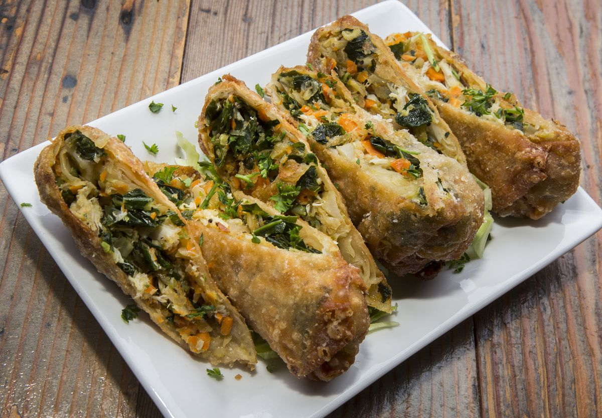 Egg rolls sliced in half on a rectangle plate with grab and collard greens and carrots.