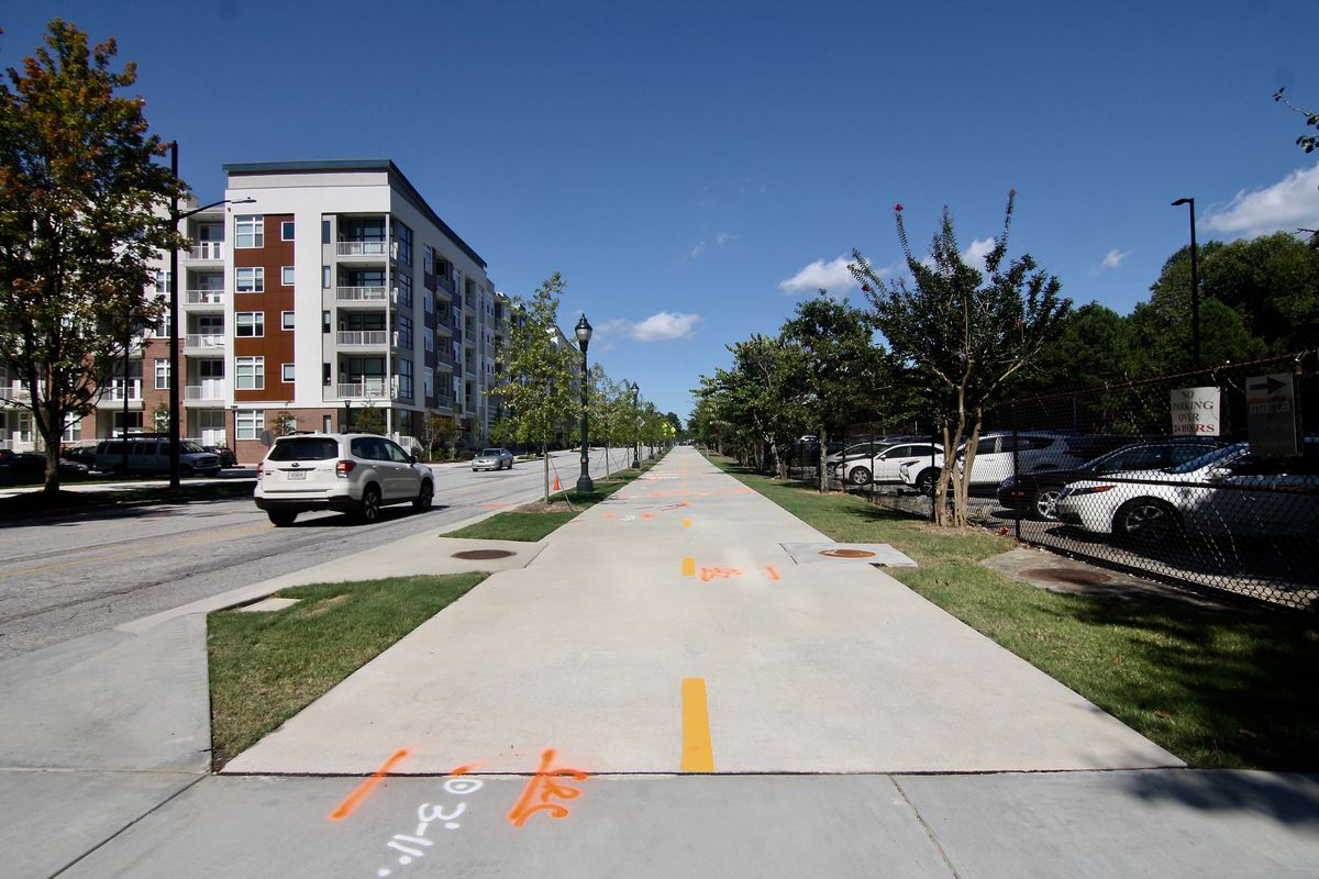 A bike path with cars parked at the right and others driving at left.