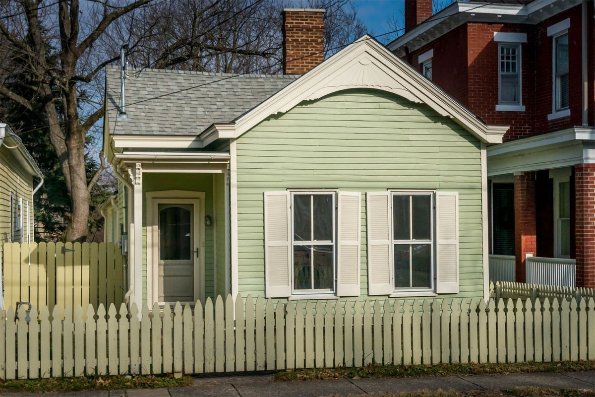 Small wood-framed house with two windows with shutters behind a low picket fence.